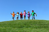 Group of multi-ethnic kids running together holding hands, on grass hill with blue sky