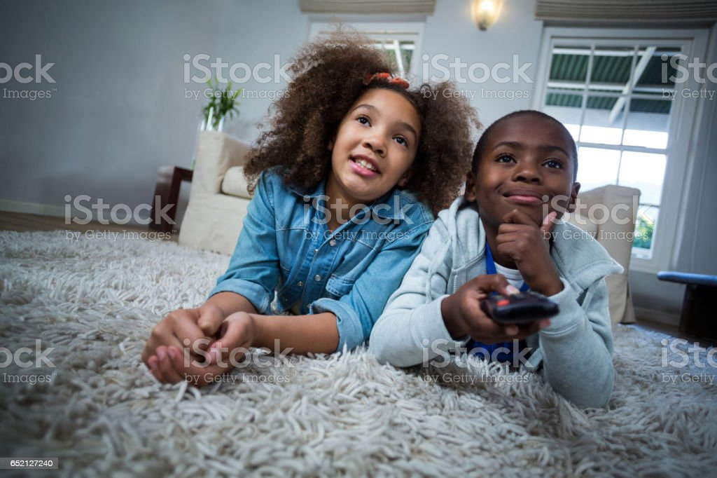 Children holding remote while lying on the floor stock photo