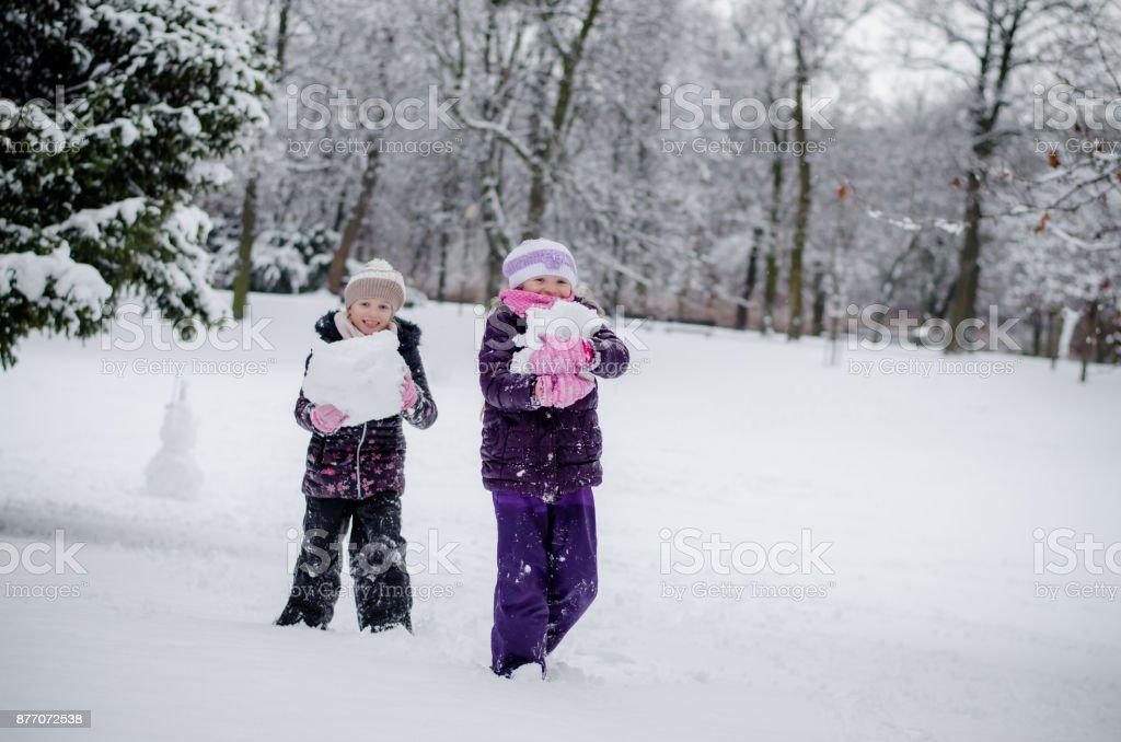 children holding snowy balls in winter park stock photo