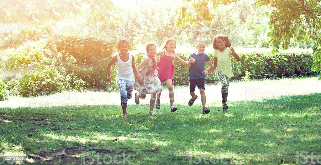 Children holding their hands and runnin stock photo