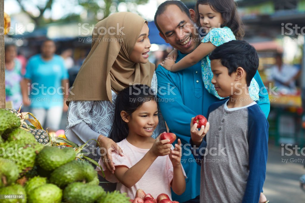 Children holding water apples by family at stall - Стоковые фото 10-11 лет роялти-фри
