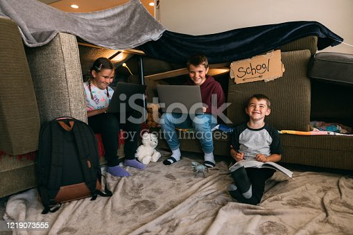Young children are working on schooling and homework from laptops inside a home. They sit inside a homemade couch fort trying their best to replicate their elementary educations while at home during the coronavirus pandemic and social distancing guidelines. Image taken in Utah, USA.