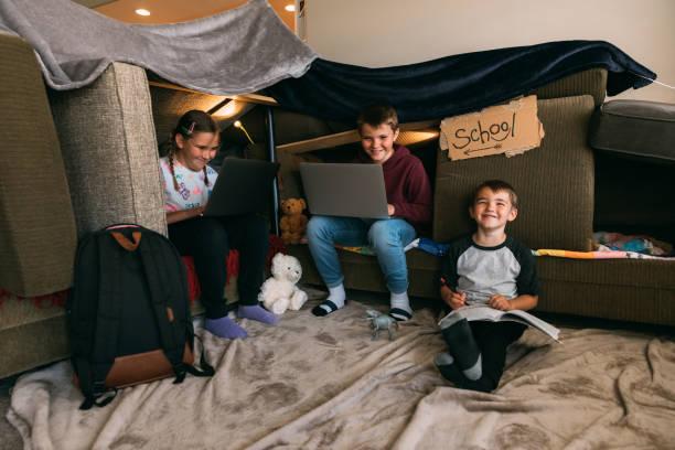 kinder homeschooling in einem couch fort - homeschooling stock-fotos und bilder