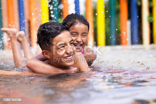 Latino children a teenage boy and an 8-year-old girl play in the pool, cuddle and cuddle in the water while smiling and having fun