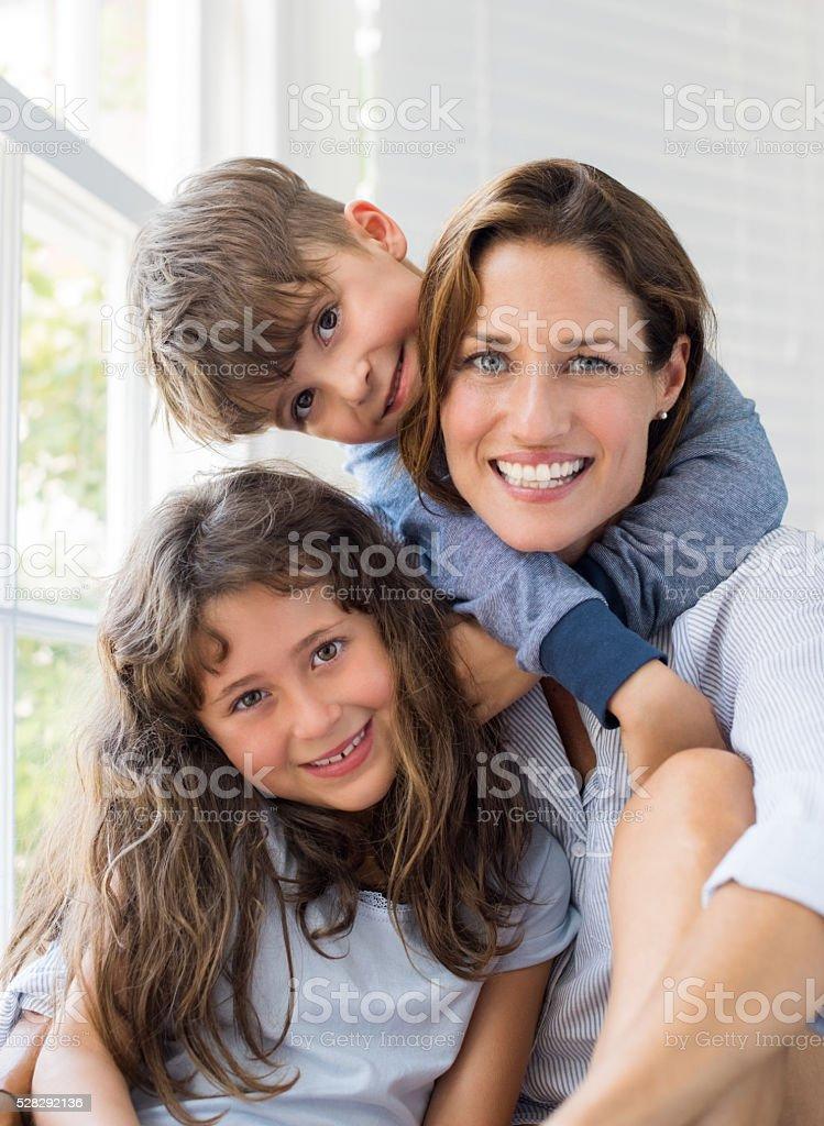Children hugging mother stock photo