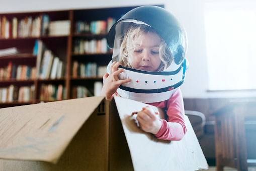 A boy and girl at home in their living room play in and color a cardboard box, one of them wearing a toy astronaut helmet.  Imagination, discovery, and fun.