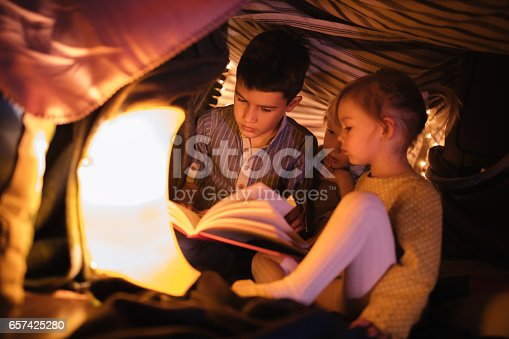 Brother reading a story to his younger siblings in a fort at night
