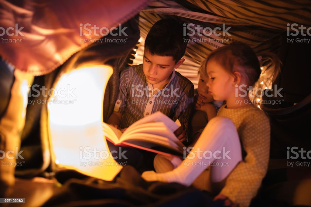 Children in a fort listening to a night story stock photo