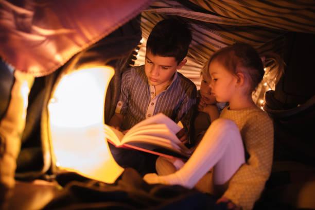 barn i ett fort som lyssnar på en natt-historia - fort bildbanksfoton och bilder