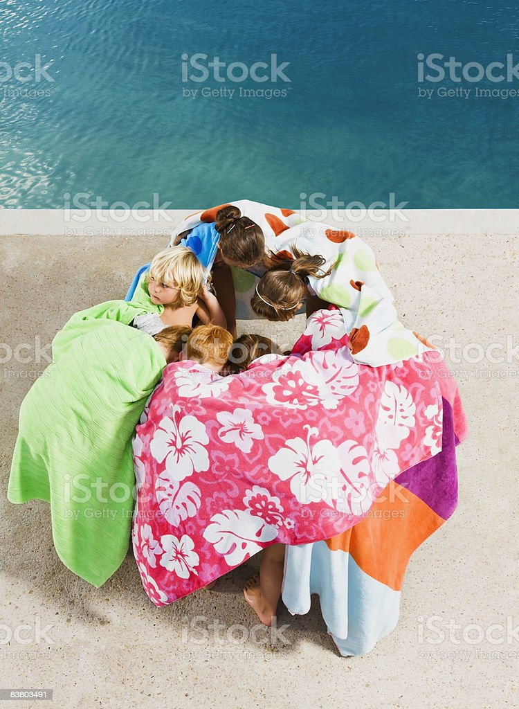 Children in a huddle by pool royalty free stockfoto