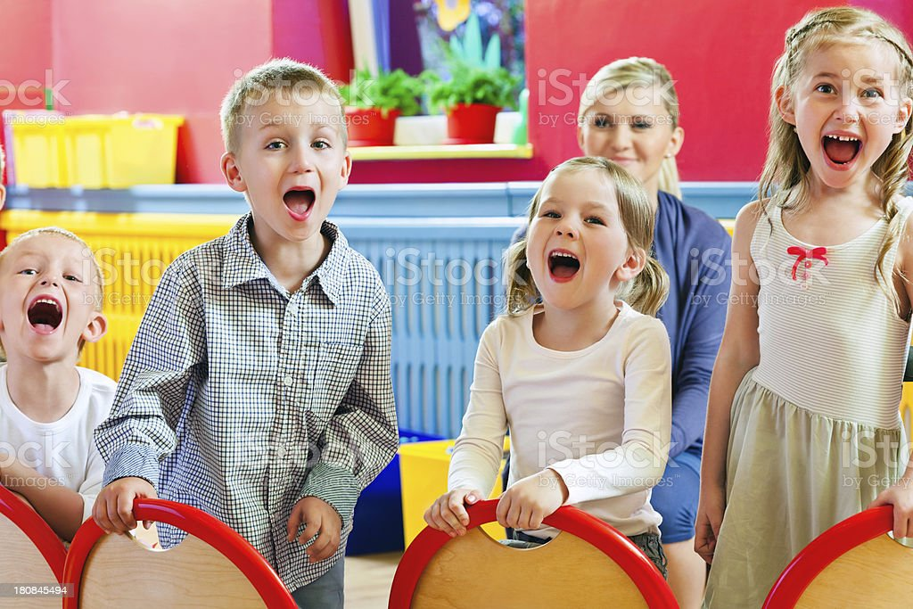 Children in a Nursery School A happy preschool children screaming at the camera with their teacher in the background. 4-5 Years Stock Photo