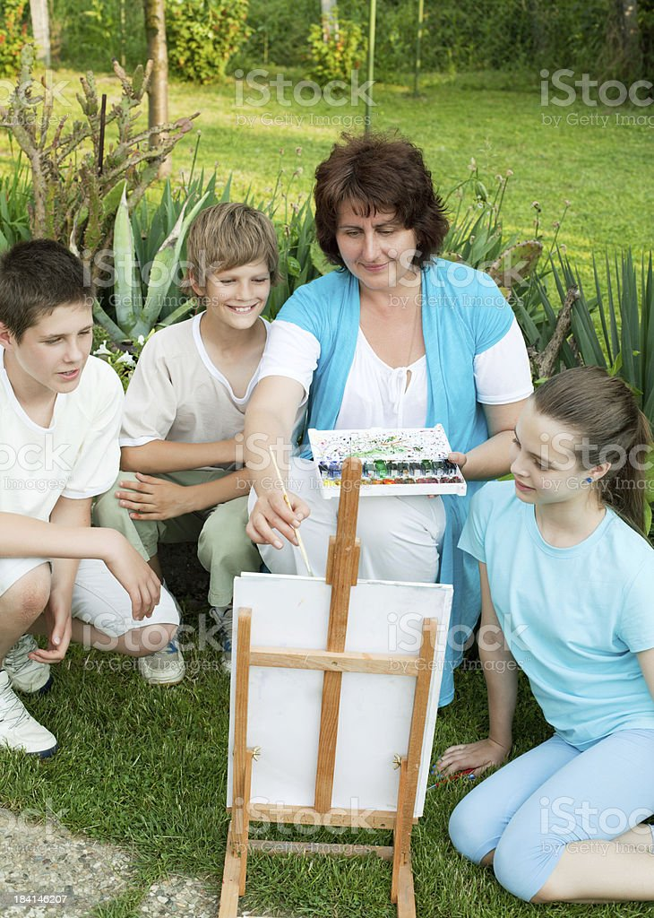 Children in art class with teacher outdoors. royalty-free stock photo