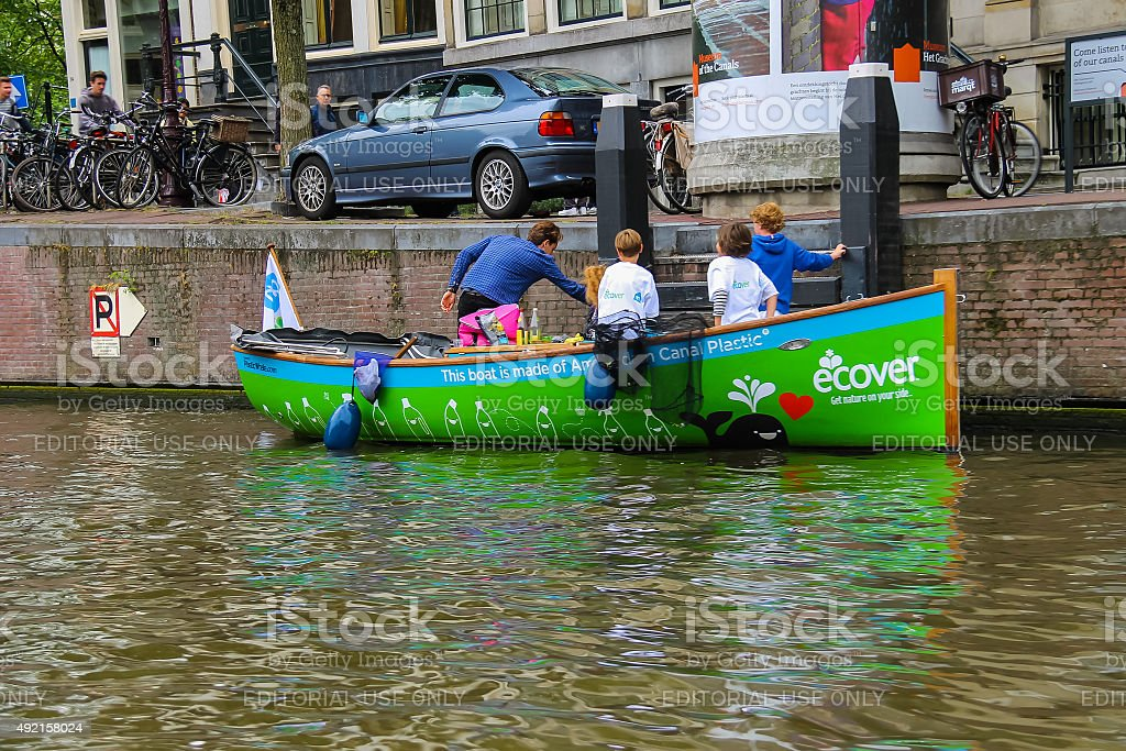 Children in boat publicizing ecological way of life on canal stock photo