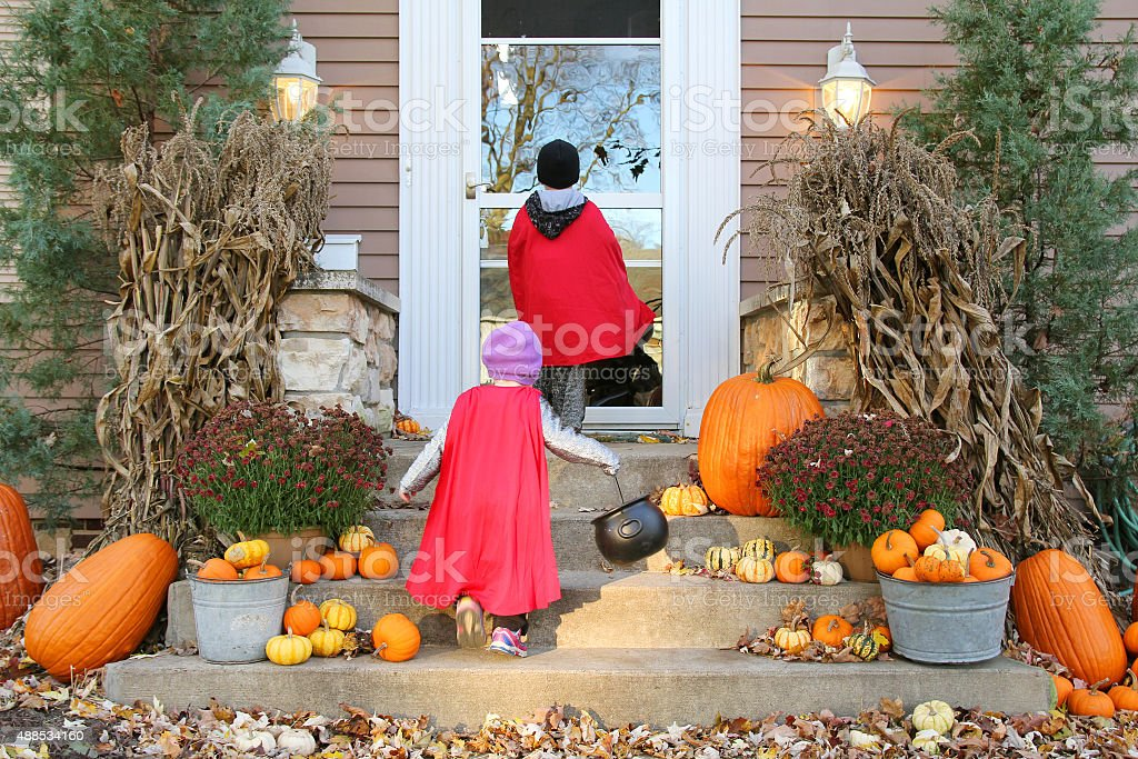 Children in Cape Costumes Trick-or-Treating on Halloween stock photo