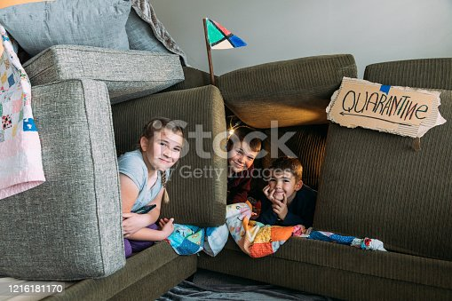 Young siblings, who are under a shelter in place order, are having fun in a couch fort quarantine. They are enjoying time playing at home. One good by product of a pandemic.