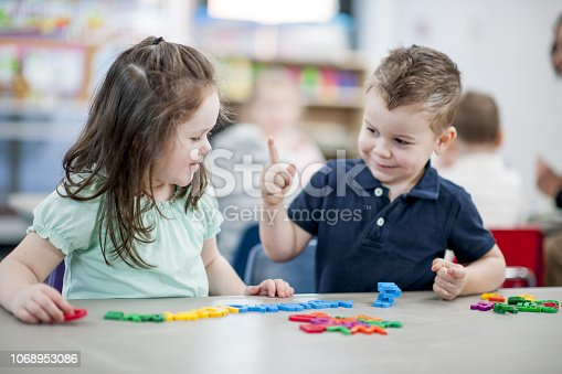 A young boy and girl are sitting in a daycare room and are playing with plastic alphabet letters.