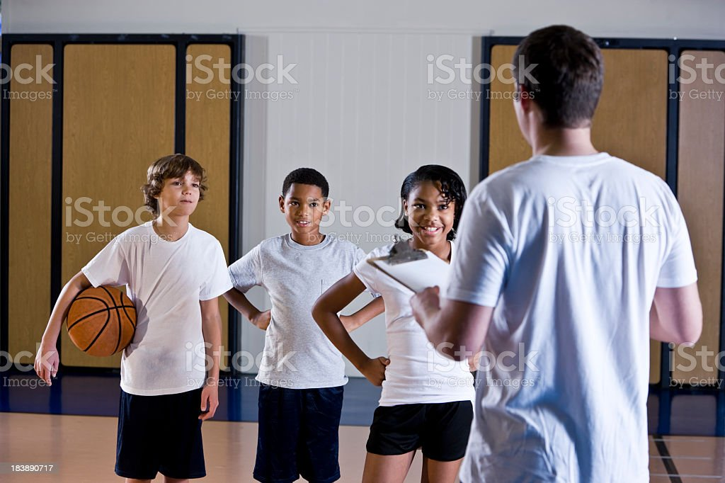 Children in gym with physical education teacher or coach stock photo