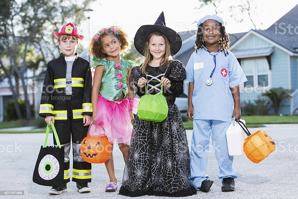 Children in halloween costumes going trick or treating stock photo