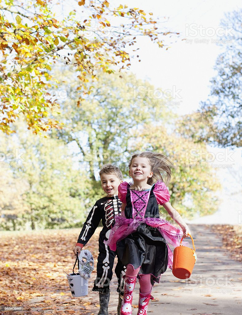 Children in Halloween costumes running in park royalty-free stock photo