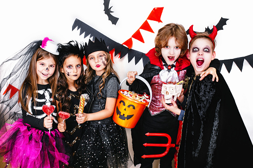 Children in halloween costumes show funny faces . Halloween party.Trick or Treat