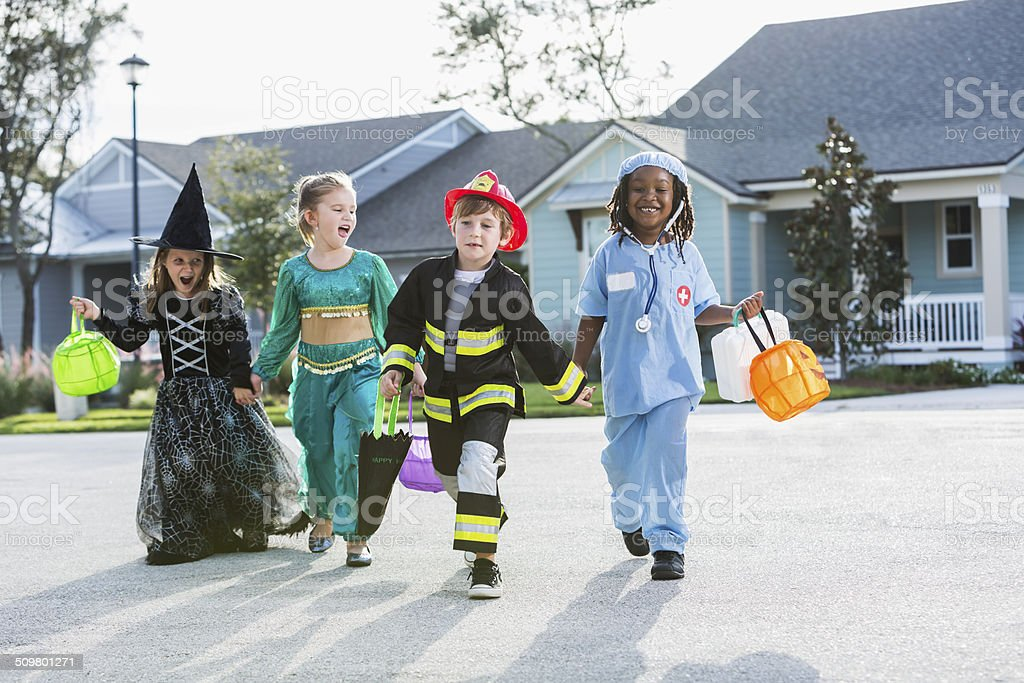 Children in halloween costumes walking down the street stock photo