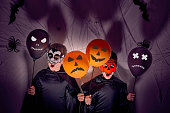 istock Children in halloween costumes with vampire and pumpkin masks holding black and orange balloons with faces on them. Dark background with shadows, spiders, spiderwebs and bats. 1269957537
