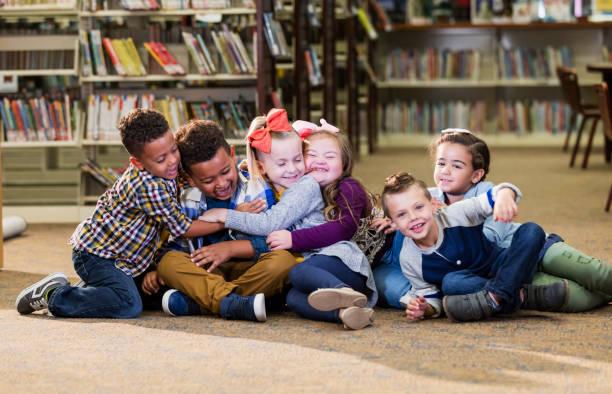 Kinder in Bibliothek, Mädchen mit Down-Syndrom, Gruppe Umarmung – Foto
