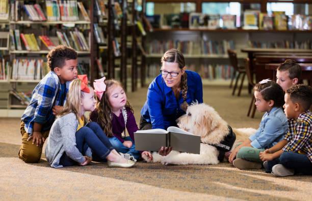 Kinder in der Bibliothek mit Lesehilfe-Hund – Foto