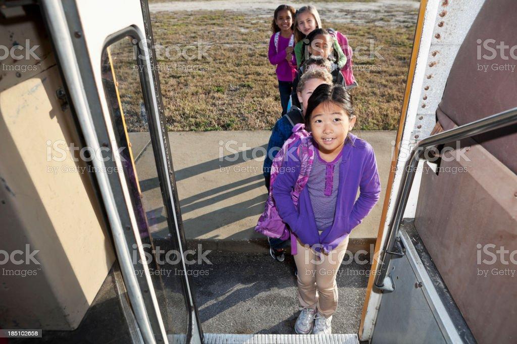 Children in line to board school bus stock photo