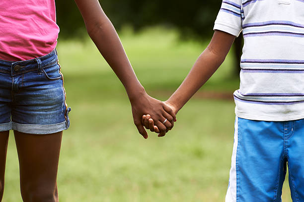 Children in love black boy and girl holding hands People in love with african little girl and boy holding hands in park. Cropped view cute teen couple stock pictures, royalty-free photos & images