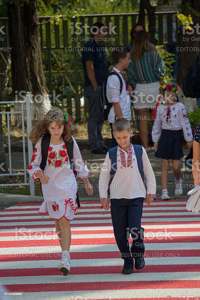 Children in national costumes back from school. Kiev, Ukraine stock photo