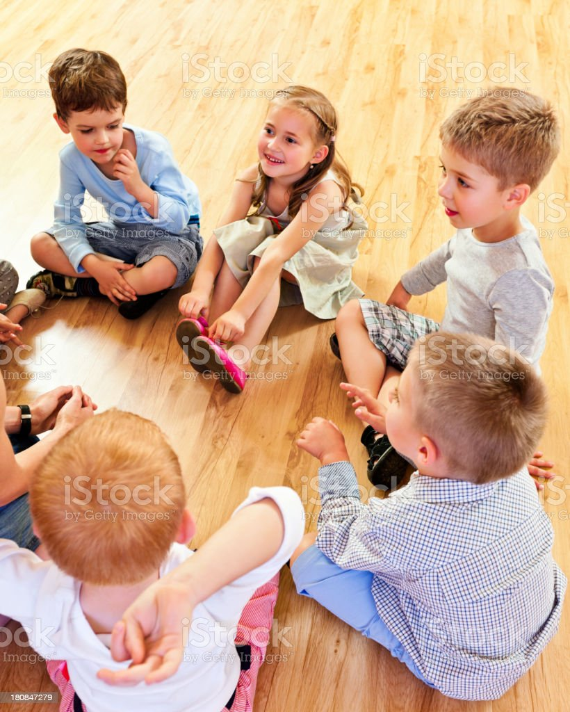 Children in Nursery School A nursery school children sitting on the floor in a circle and listening to their teacher. 4-5 Years Stock Photo