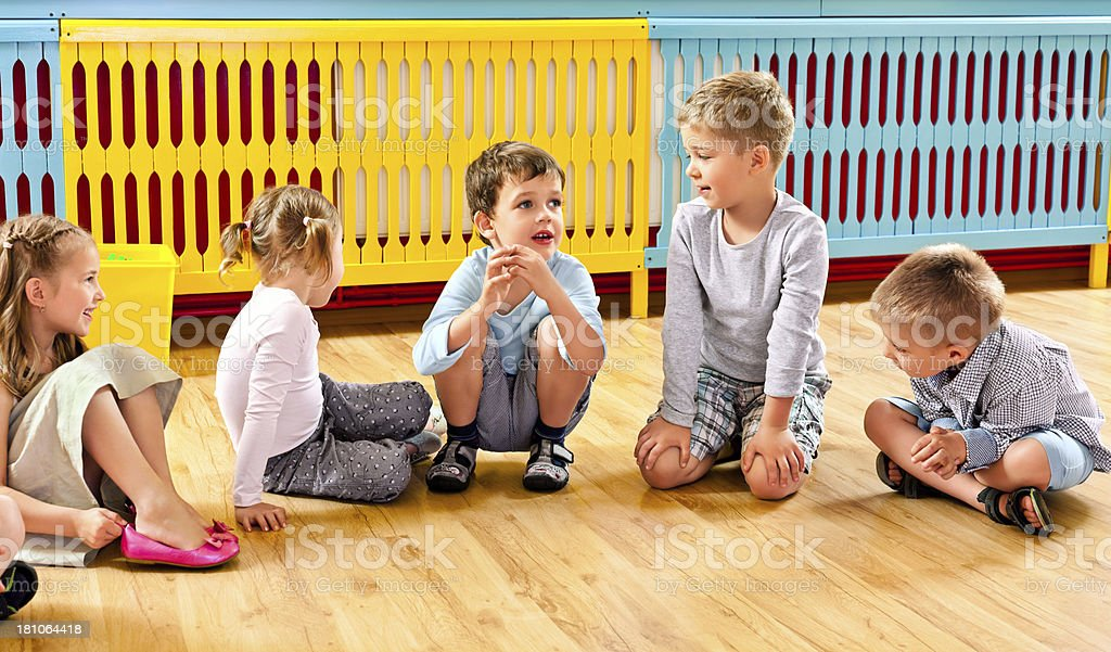 Children in Nursery School A nursery school children sitting on the floor in a playroom and talking. 4-5 Years Stock Photo