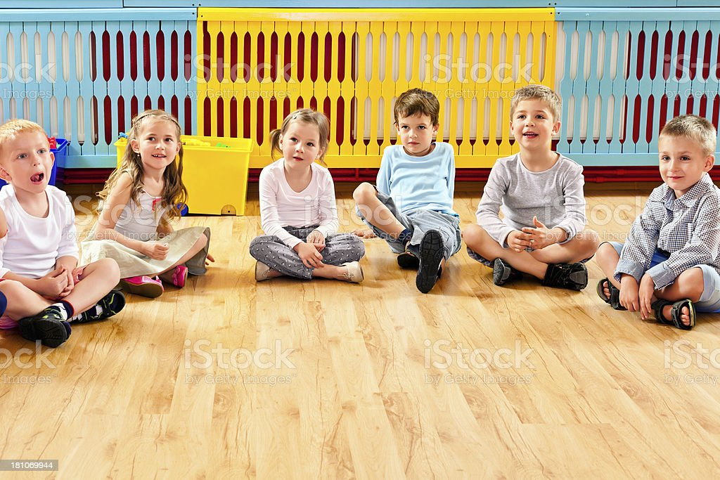 Children in Nursery School A nursery school children sitting on the floor in a playroom and listening to their teacher. 4-5 Years Stock Photo