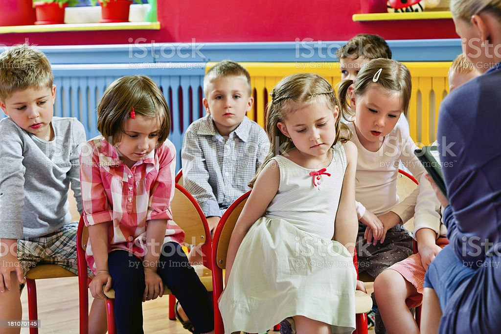 Children in Nursery School A  bored preschool children sitting in a row in a classroom and listening to their teacher. 4-5 Years Stock Photo
