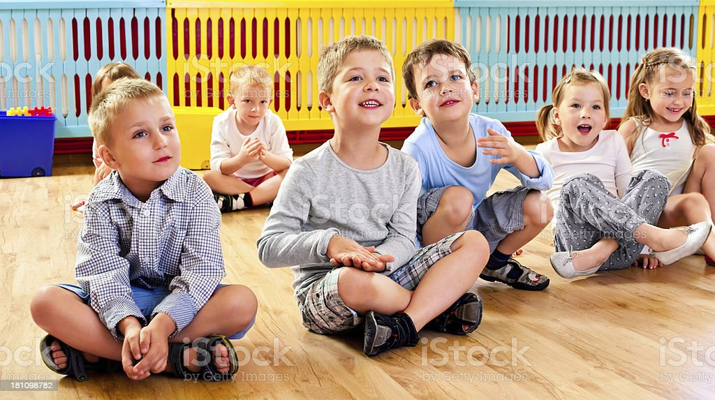Children in Nursery School A nursery school children sitting on the floor in a playroom and listening to their teacher. 4-5 Years Stock Photo