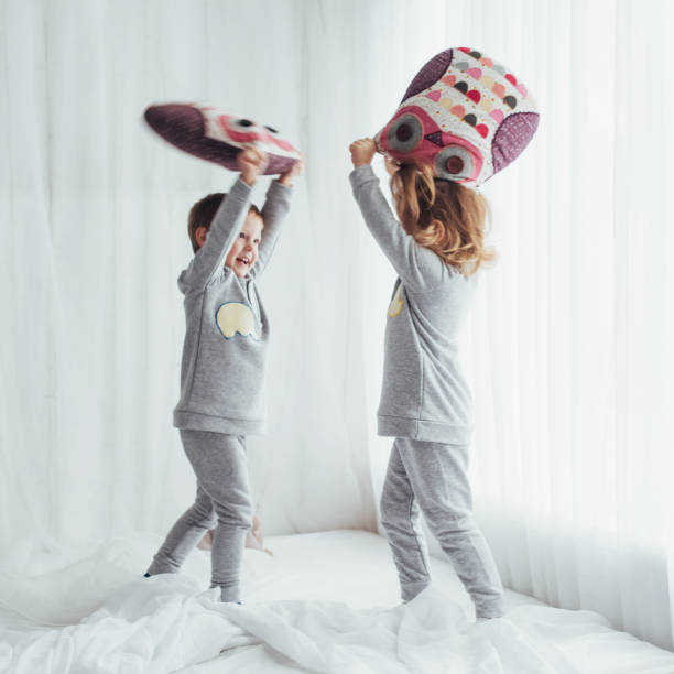 Children in pajamas Children in soft warm pajamas playing in bed flight suit stock pictures, royalty-free photos & images