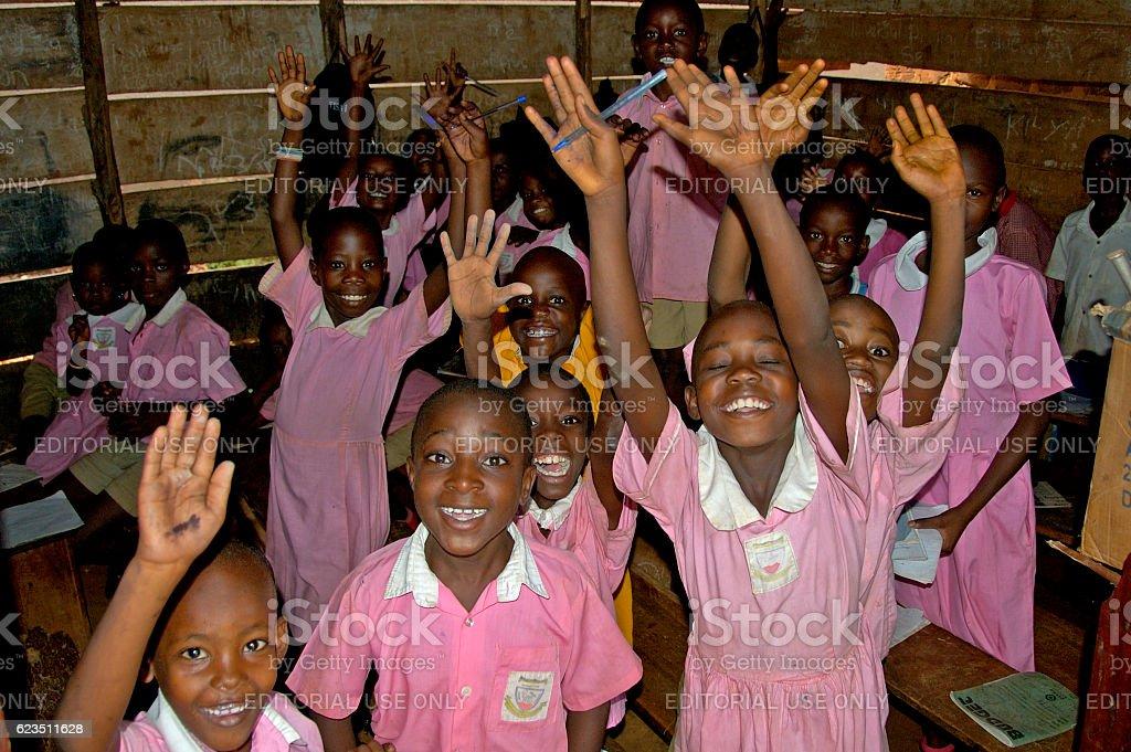 Children in pink school uniform in their school waving. stock photo