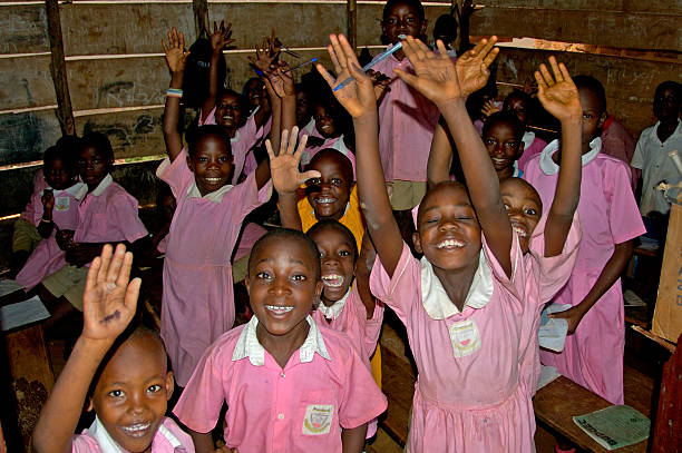Children in pink school uniform in their school waving. stock photo