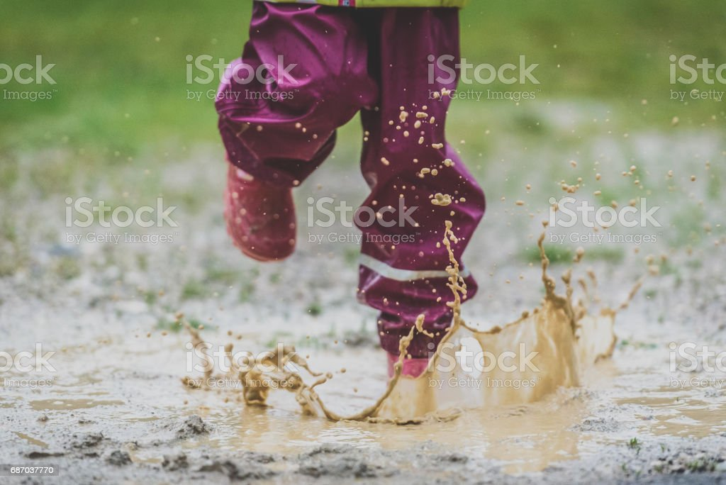 Children in rubber boots and rain clothes jumping puddle defocused. Lizenzfreies stock-foto