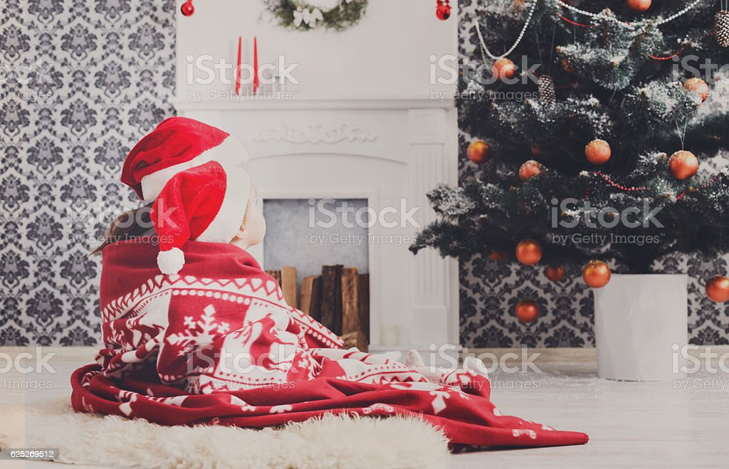 Children in santa hats near christmas tree, wait for holidays stock photo
