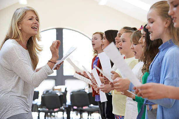 children in singing group being encouraged by teacher - middle school teacher stock pictures, royalty-free photos & images