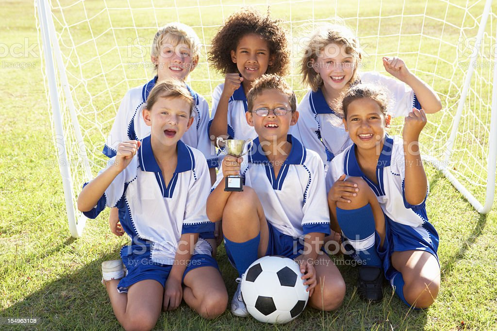 Children In Soccer Team Celebrating With Trophy stock photo
