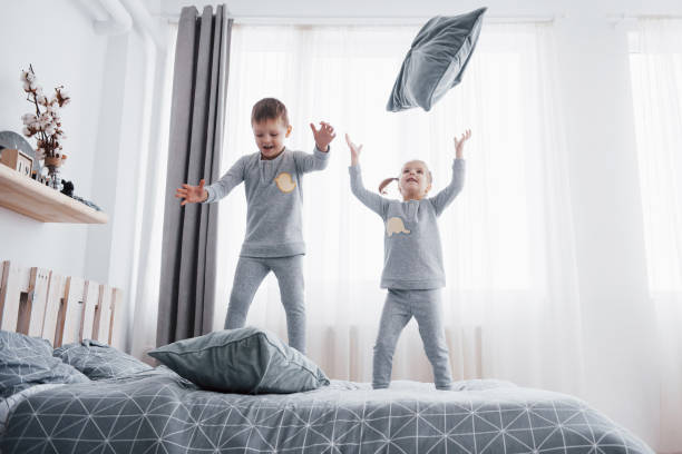Children in soft warm pajamas playing in bed Happy kids playing in white bedroom. Little boy and girl, brother and sister play on the bed wearing pajamas. Nursery interior for children. Nightwear and bedding for baby and toddler. Family at home bib overalls boy stock pictures, royalty-free photos & images