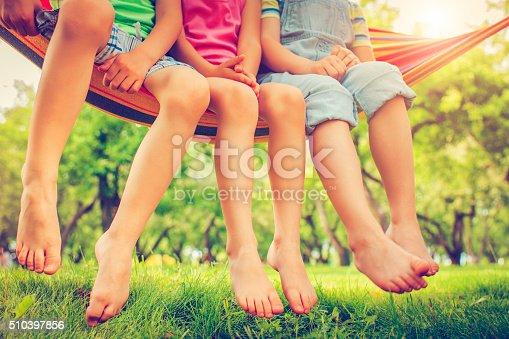 Three happy children in hammock in a park or back yard in summer
