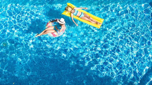 Children in swimming pool aerial drone view fom above, happy kids swim on inflatable ring donut and mattress, active girls have fun in water on family vacation on holiday resort stock photo