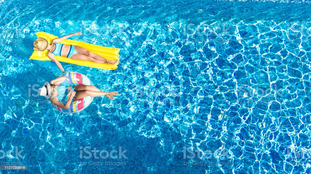Children in swimming pool aerial drone view fom above - Swimming pool girl christmas vacation ...