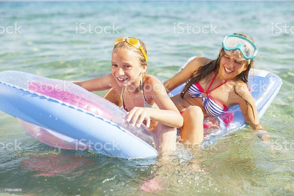 Children in the Sea siting on a  inflatable beach mattress royalty-free stock photo