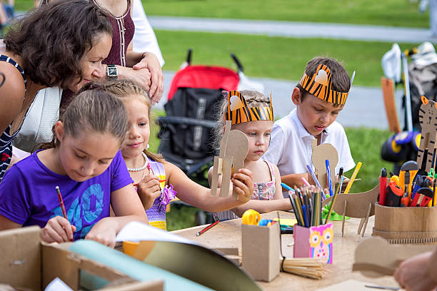 children in tiger costumes draw and create crafts - Photo