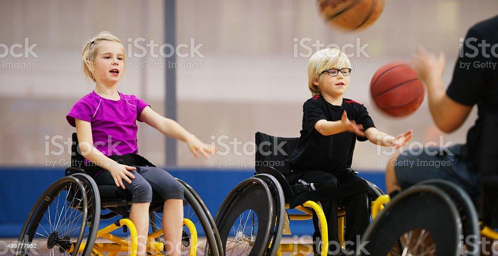 Crianças em cadeira de rodas, passando as bolas de basquete - foto de acervo